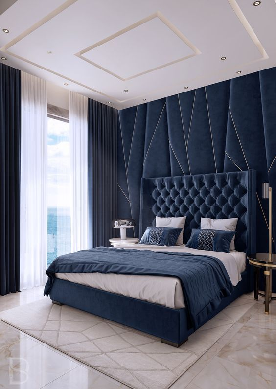 navy velvet and a statement headboard wall make the space wow, and gold touches add to this luxury