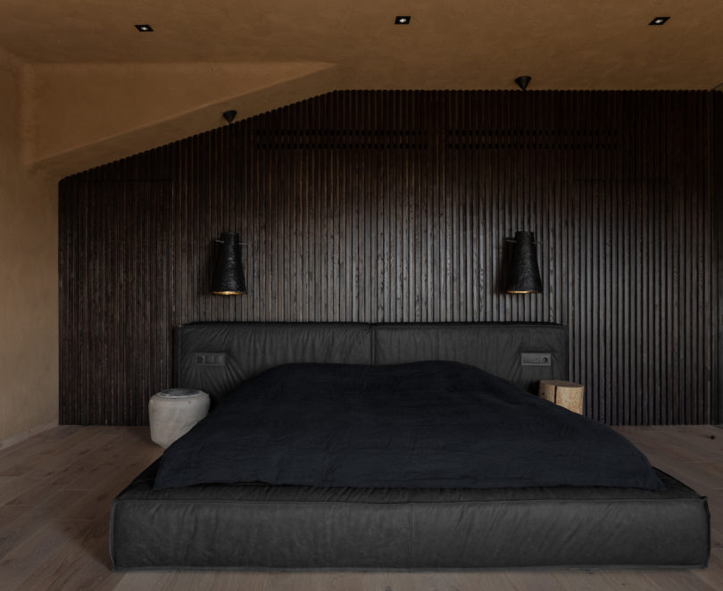 The bedroom is dark and soothing, with a wood clad wall, an upholstered dark bed and wall sconces