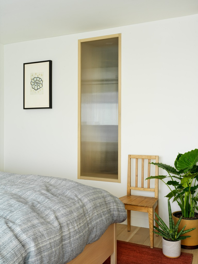 The bedroom is done with potted plants, simple and comfy furniture and a window