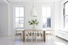 04 This is a dining space with a wooden table, white chairs and pendant lamps – this space is filled with light and features cool views