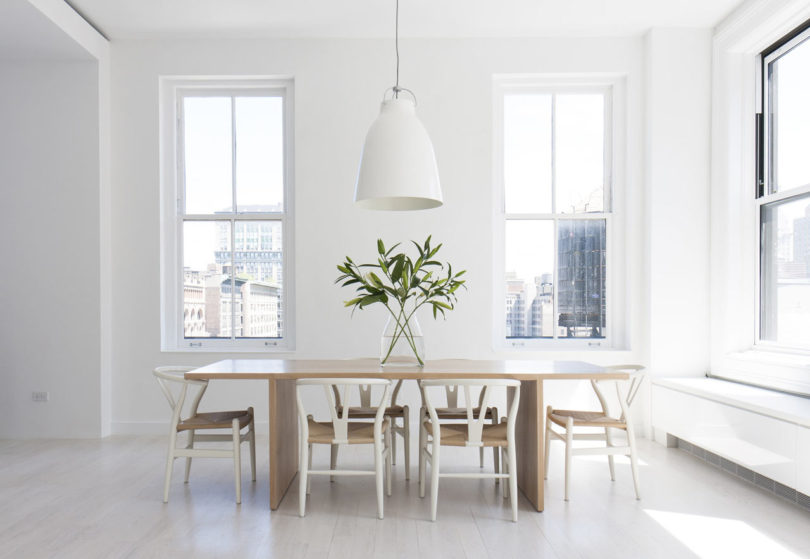 This is a dining space with a wooden table, white chairs and pendant lamps   this space is filled with light and features cool views