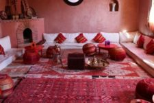 04 a bold red space done with Moroccan touches – patchwork poufs, striped pillows, a large hearth with musical instruments on the mantel