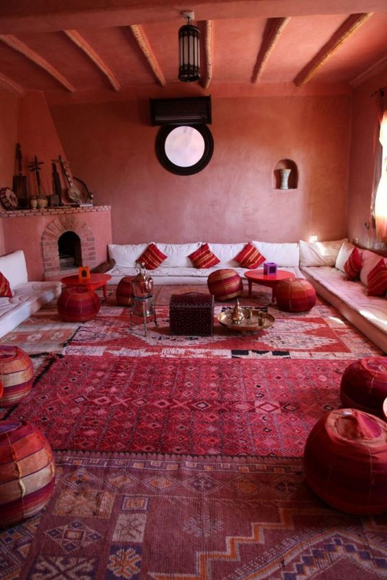 a bold red space done with Moroccan touches - patchwork poufs, striped pillows, a large hearth with musical instruments on the mantel