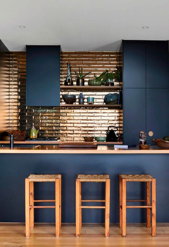 a sleek navy kitchen with a copper tile backsplash, matching countertops and chairs