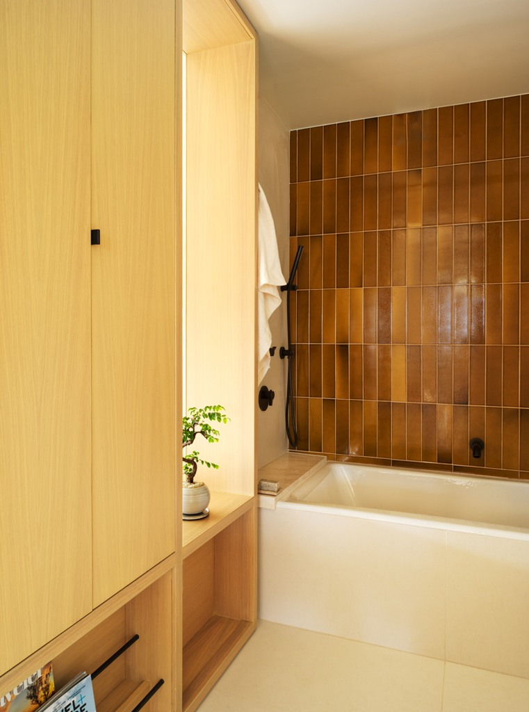 The bathroom features much storage space hidden within the wardrobes and tiles of a very quirky earthy shade