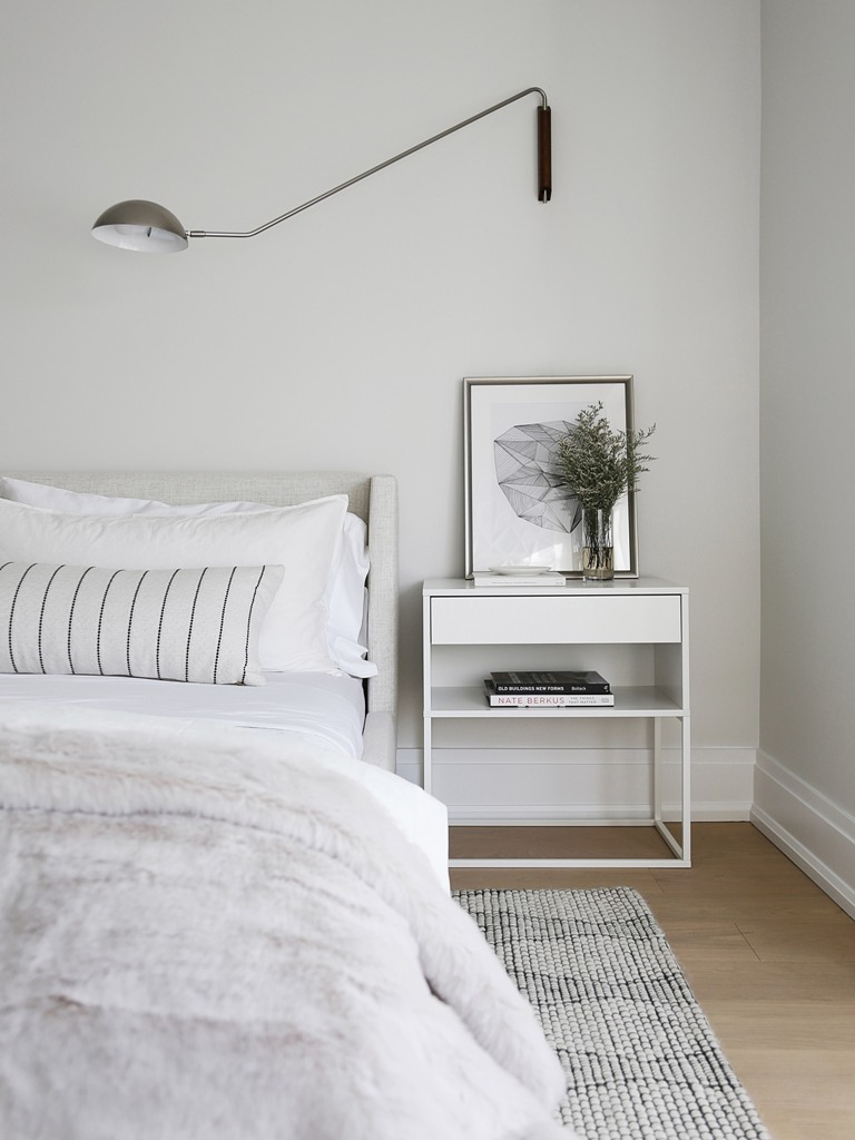 The bedroom is all-neutral, with some prints and simple and stylish furniture