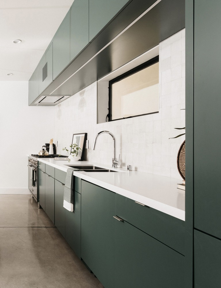 The kitchen is designed in dark green and white, with a chic tile backsplash and a matching white countertop