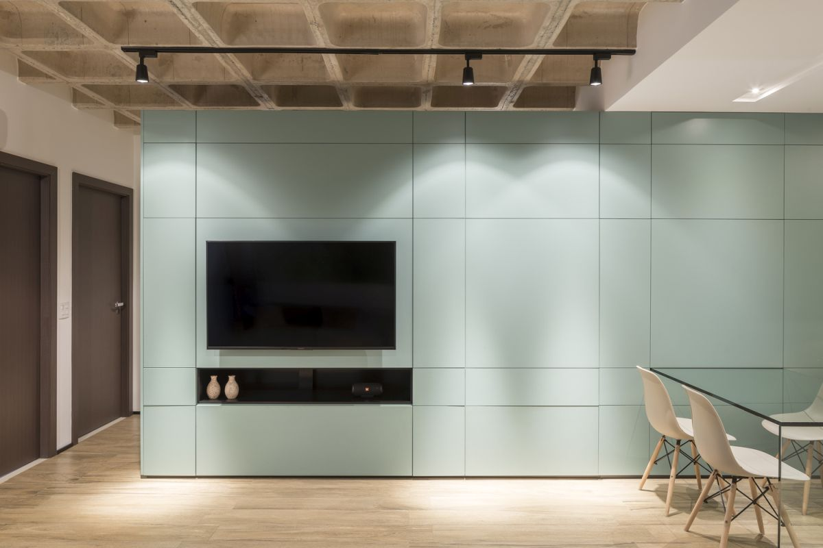 The large custom cabinet serves as an entertainment center for the living room and as a space divider