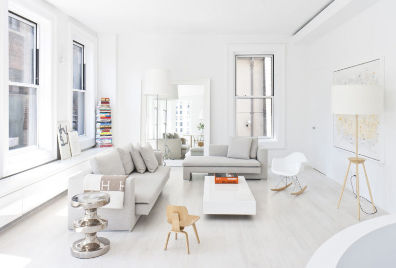 The living room features some comfortable grey furniture, a stack of colorful books and a world map plus lots of light