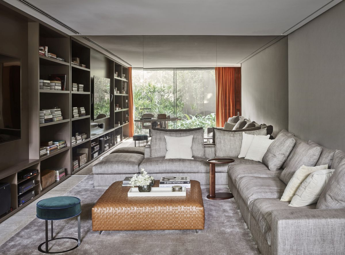 The living room is done with a ashy shelving unit, grey furniture and a leather ottoman