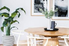 05 a chic coastal dining room with a wooden round table, a jute rug and lots of greenery