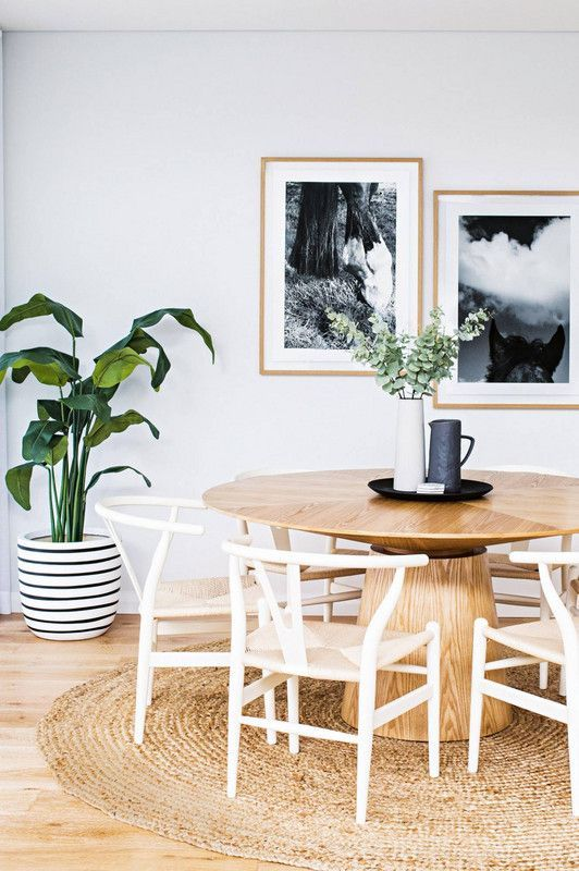 a chic coastal dining room with a wooden round table, a jute rug and lots of greenery
