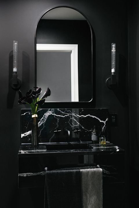 a chic moody bathroom in black and graphite grey with a marble wall-mounted sink