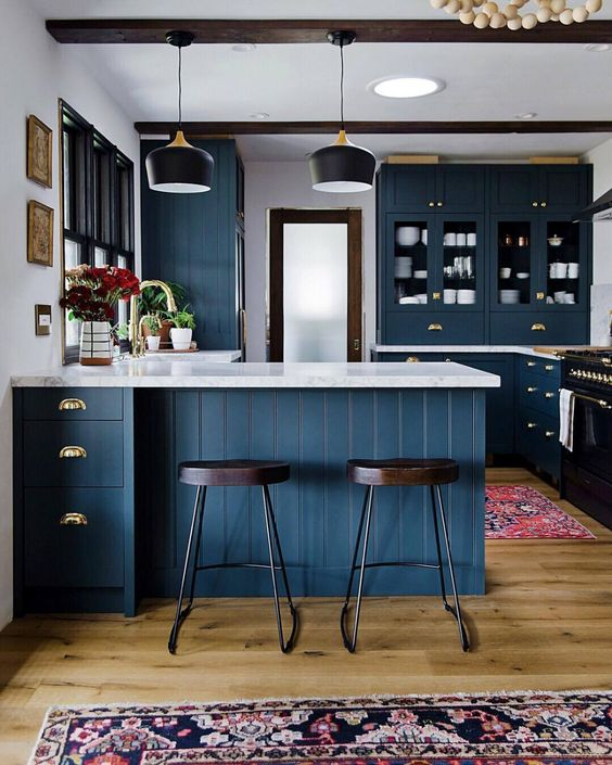 a chic navy kitchen with white stone countertops, dark wooden beams and chairs for a contrast
