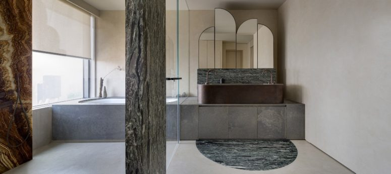 The bathroom features truly wabi-sabi, with wooden and marble pillars a stone clad tub and timber