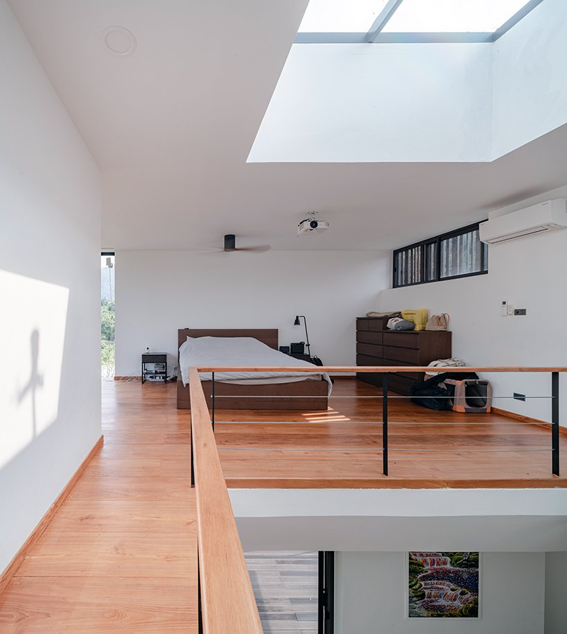 The bedroom features some dark stained furniture, lamps and a large skylight that brings much light in