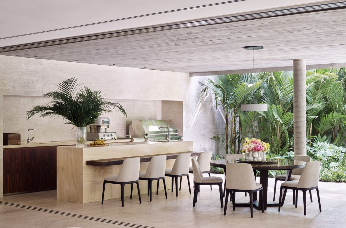The kitchen features only lower cabinets, a stone kitchen island and a chic dining space opened to outdoors