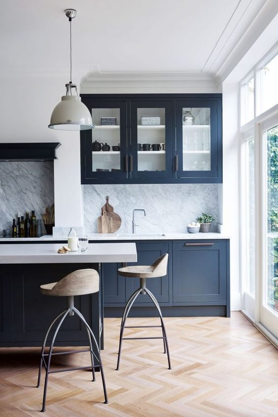 a bold navy kitchen with white countertops and a stone backsplash and pendant lamps is super chic