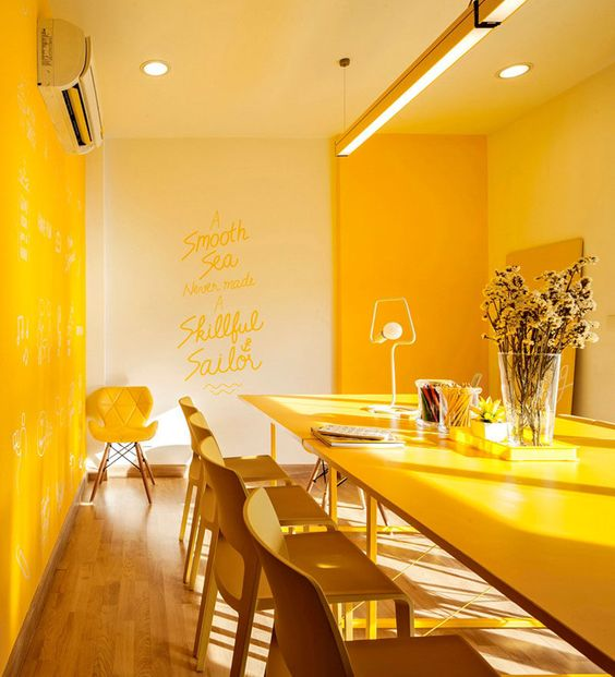 an ultra modern dining space done in yellow   with bright furniture, built in lights and yellow chairs