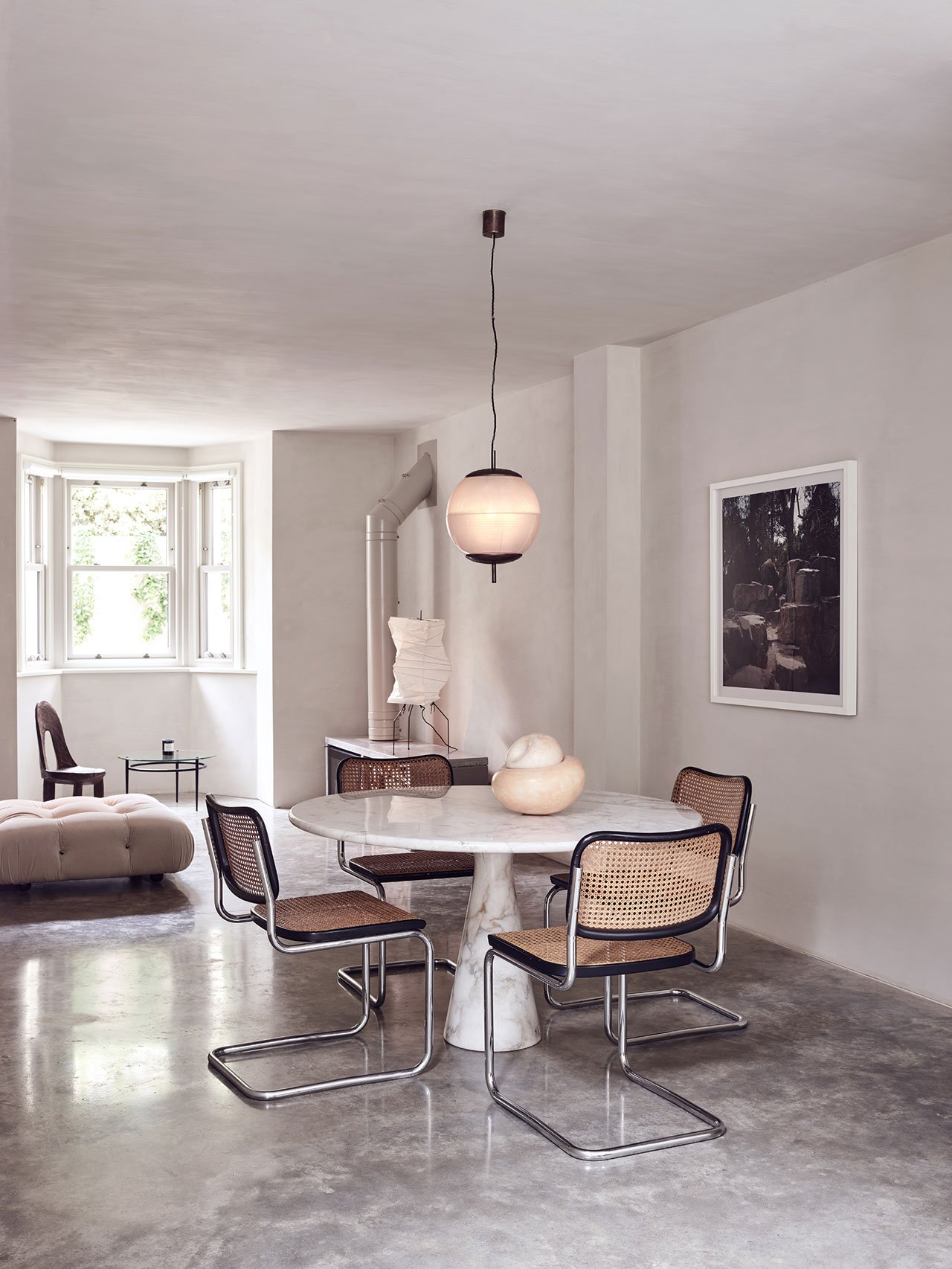 The dining space is done with a marble table and wicker chairs, there's a chic lamp