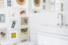 07 The powder room is done with a colorful gallery wall, sleke white appliances and a large mirror
