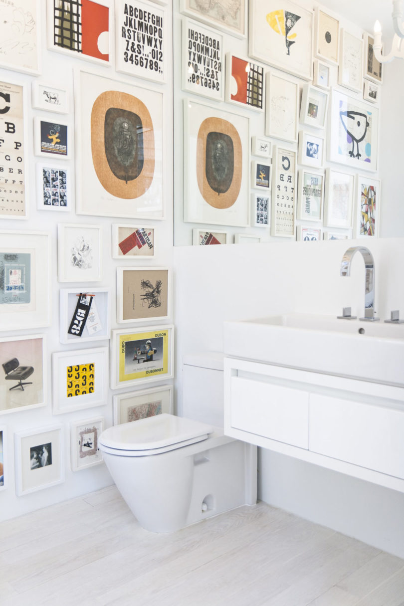 The powder room is done with a colorful gallery wall, sleke white appliances and a large mirror