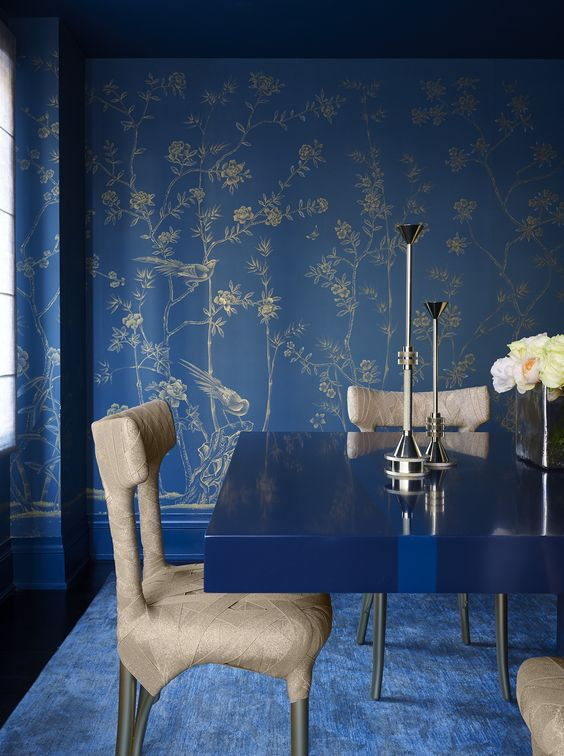 a bright blue living room with botanical printed wallpaper, a modern table and wrapped chairs
