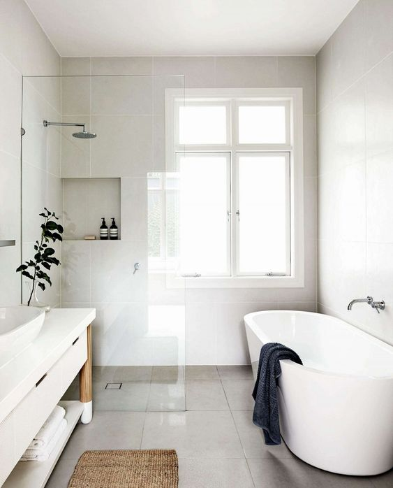 a clean and neutral minimalist bathroom done with neutral tiles and a white vanity and bathtub