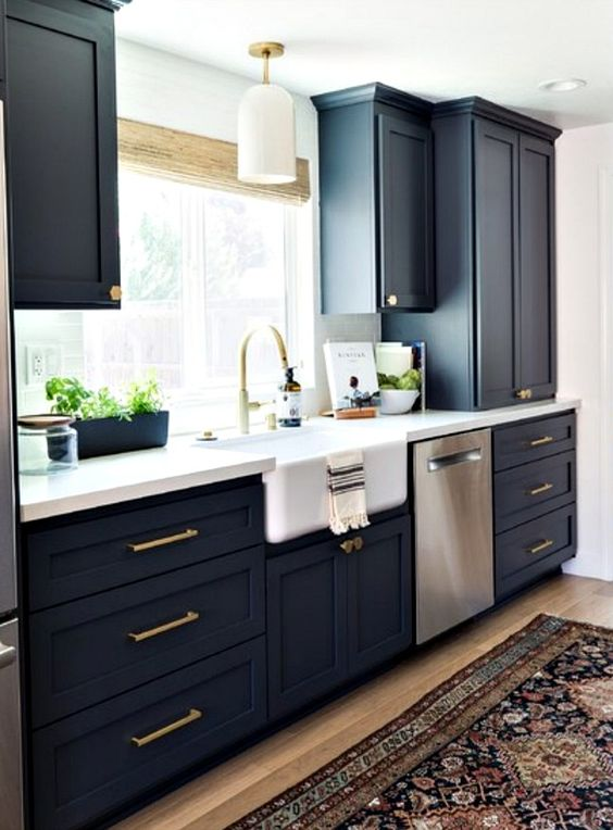 a stylish navy kitchen with gold fixtures and handles, a white countertop and chic lamps