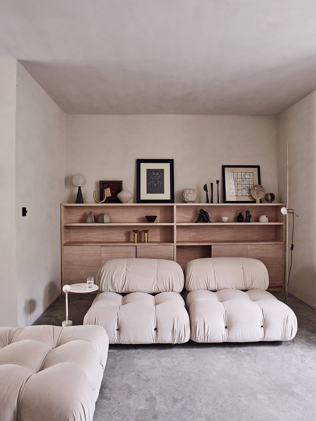 The living room is done with neutral loungers and a large shelving unit