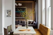 08 a chic dining room with a stone slab table, leather chairs and a large amber-colored leather bench