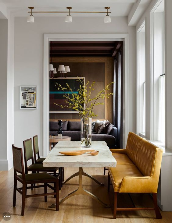 a chic dining room with a stone slab table, leather chairs and a large amber-colored leather bench