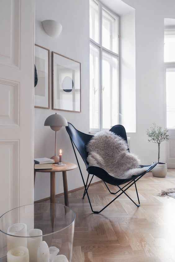 a light-filled living room with white walls and a light-colored parquet floor plus furniture on legs