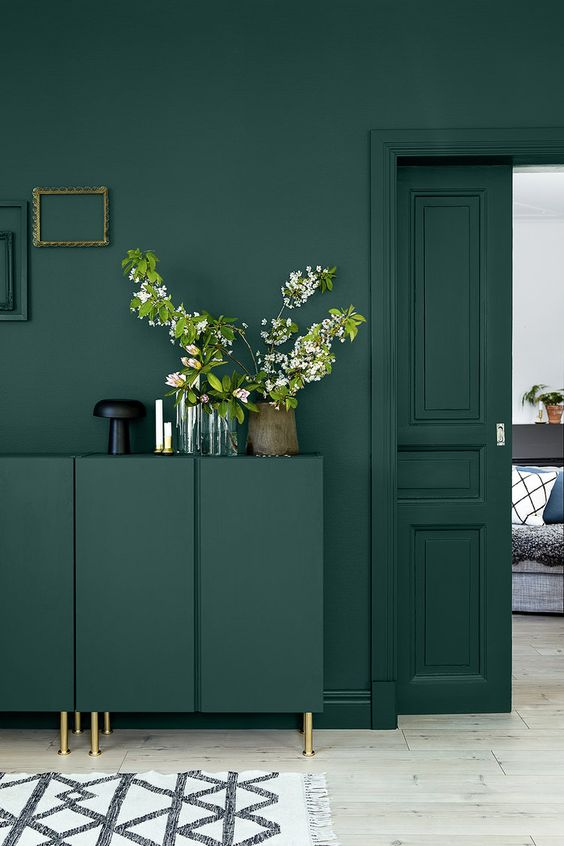 a monochromatic emerald green interior spruced up with gold touches and frames on the wall