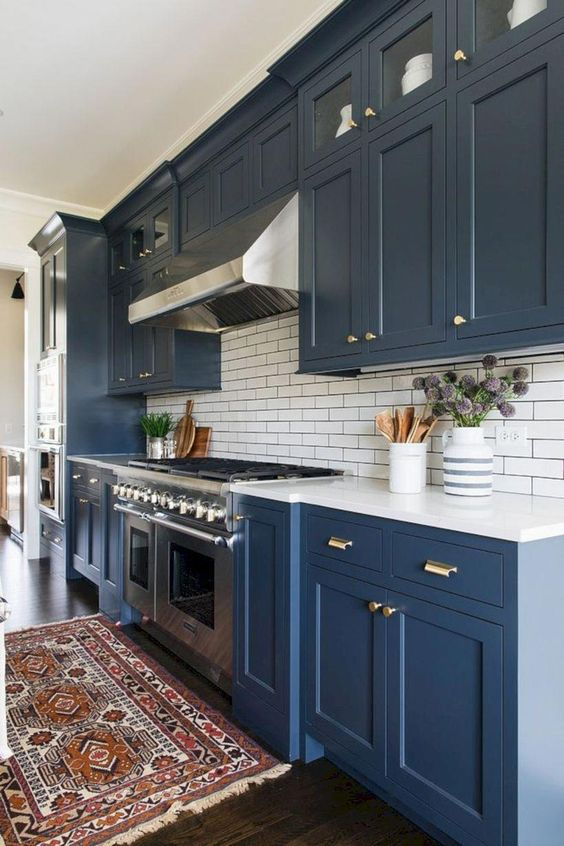 a navy kitchen with gold touches, a subway tile backsplash and a boho rug to add color to the space