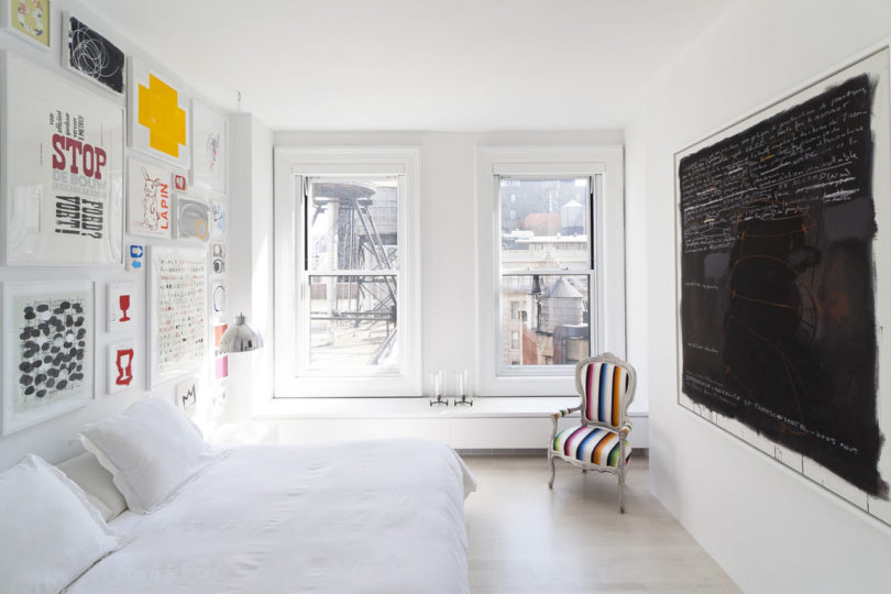 The bedroom is done with a bright gallery wall, a large chalkboard and a cozy bed