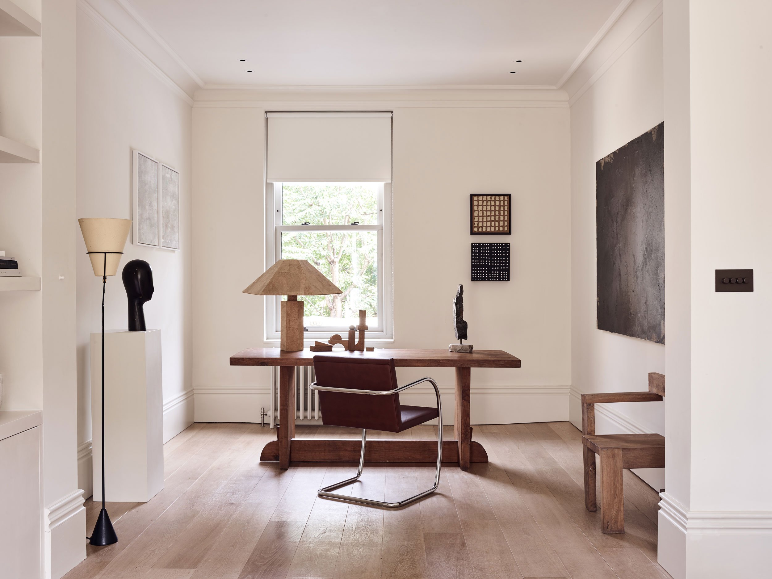 The home office features a chic wooden desk and a leather chair plus some art
