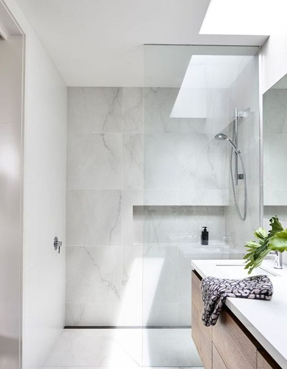 a chic and clean minimalist bathroom done with white marble tiles and a skylight to make the space more welcoming