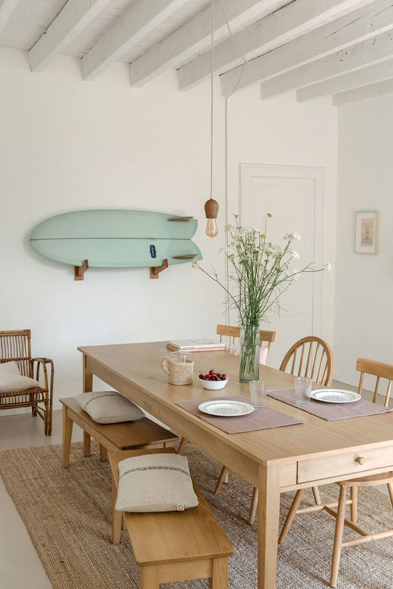 a coastal dining room with a simple wooden table and some mini benches that match - the furniture perfectly matches the style