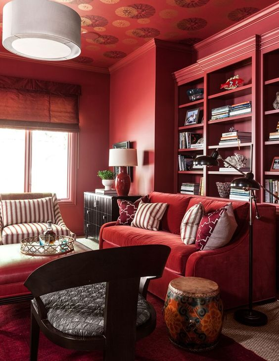 a monochromatic bold red living room with built in shelves, comfy furniture and some dark touches for drama