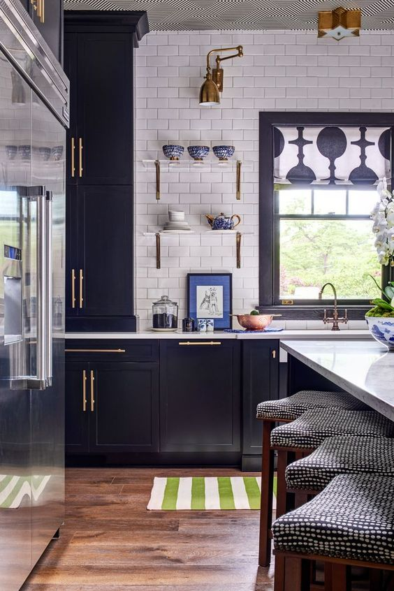 a navy kitchen with gold touches, a white subway tile backsplash and patterns feels retro and very chic
