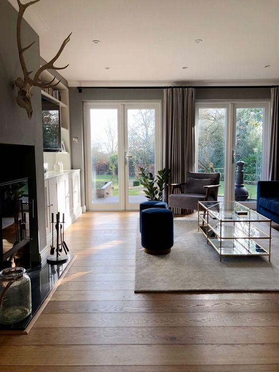 a stylish living room with grey floor-length curtains that make the space look taller and larger