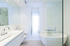 10 The bathroom is done in white, with lots of lights, a sleek floating vanity and a free-standing tub