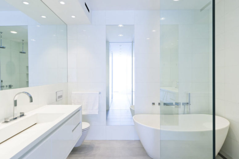 The bathroom is done in white, with lots of lights, a sleek floating vanity and a free-standing tub