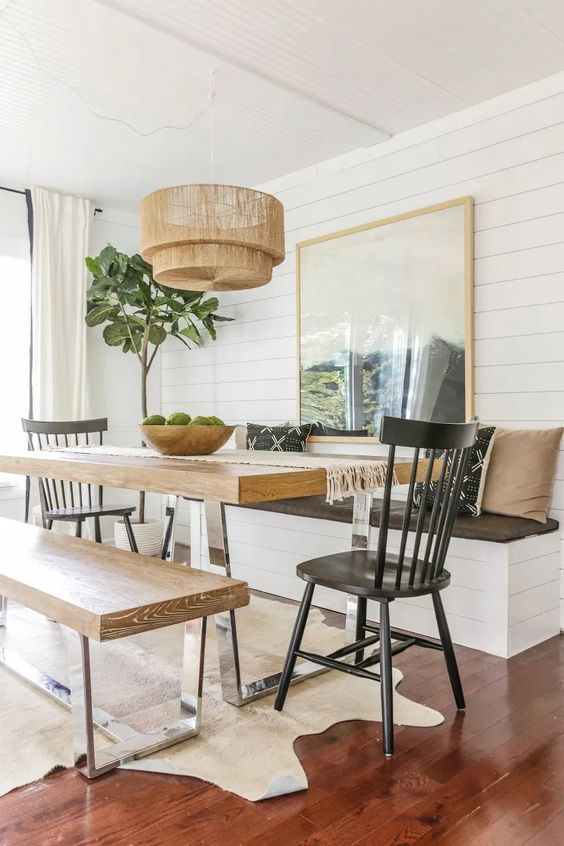 a cozy dining space with a table on a metal base and matching benches that repeat the table design