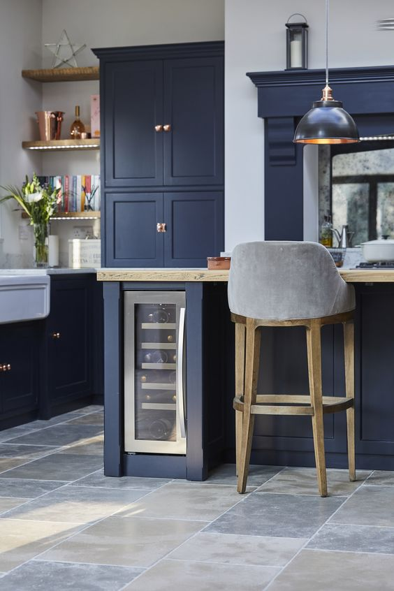 a retro navy kitchen with white and light-colored wood touches and touches of copper that make it feel cozy