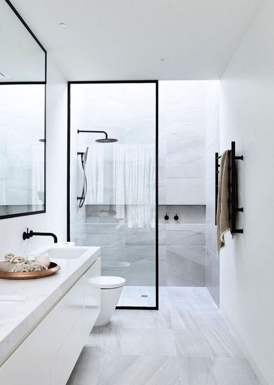 a stylish minimmalist bathroom done with grey marble tiles and touches of black for drama