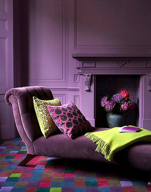 a very refined deep purple living room with matte walls and an exquisite velvet daybed with pillows