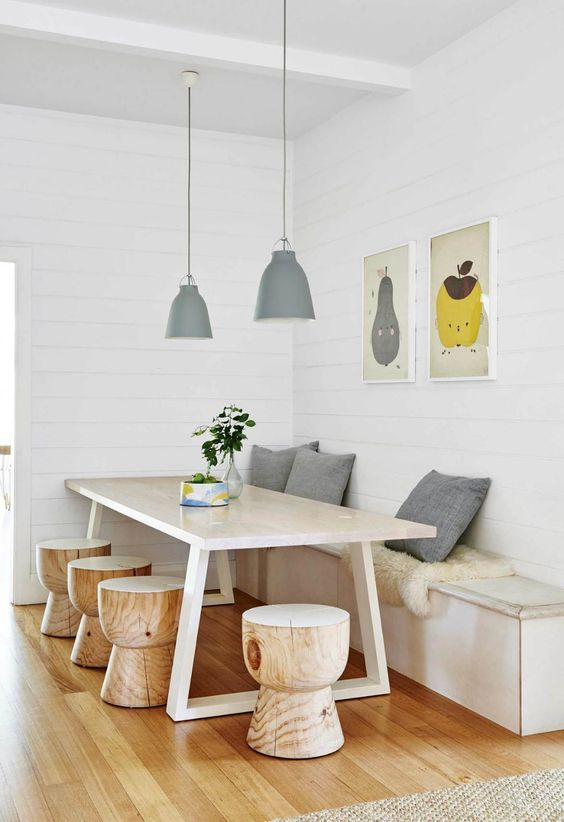 a chic dining space with a storage bench, a stylish wooden table and little round stools