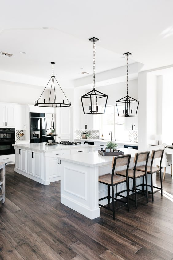 a large neutral kitchen with two kitchen islands - one for cooking and another for eating